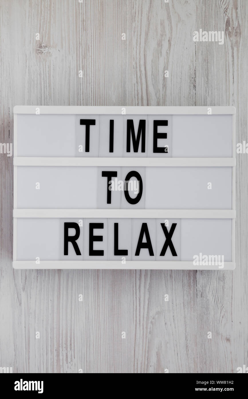 'Time to relax' words on a modern board over white wooden surface, top view. Overhead, from above. Flat lay. Close-up. Stock Photo