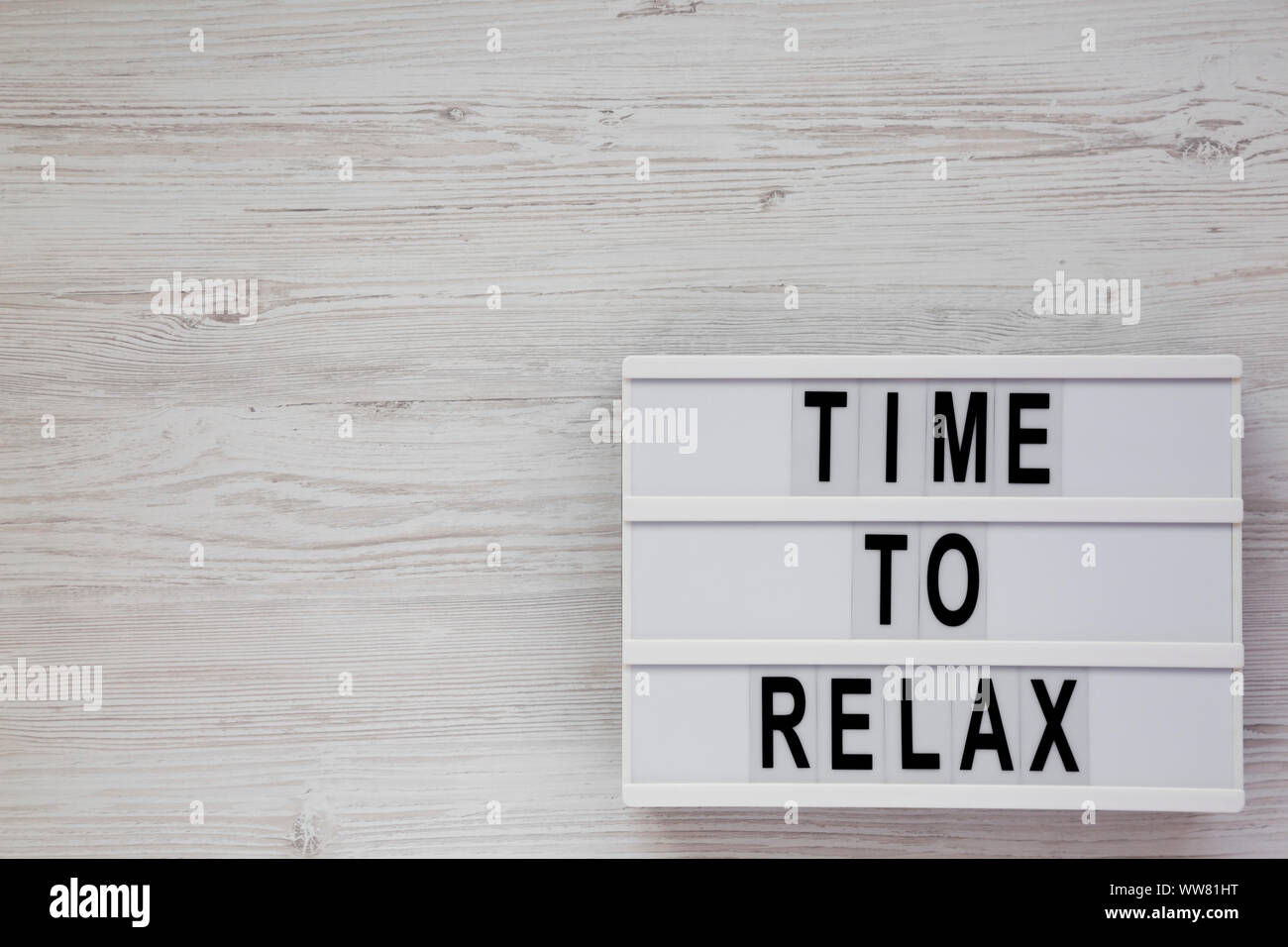 'Time to relax' words on a lightbox on a white wooden background, top view. Overhead, from above. Flat lay. Copy space. Stock Photo