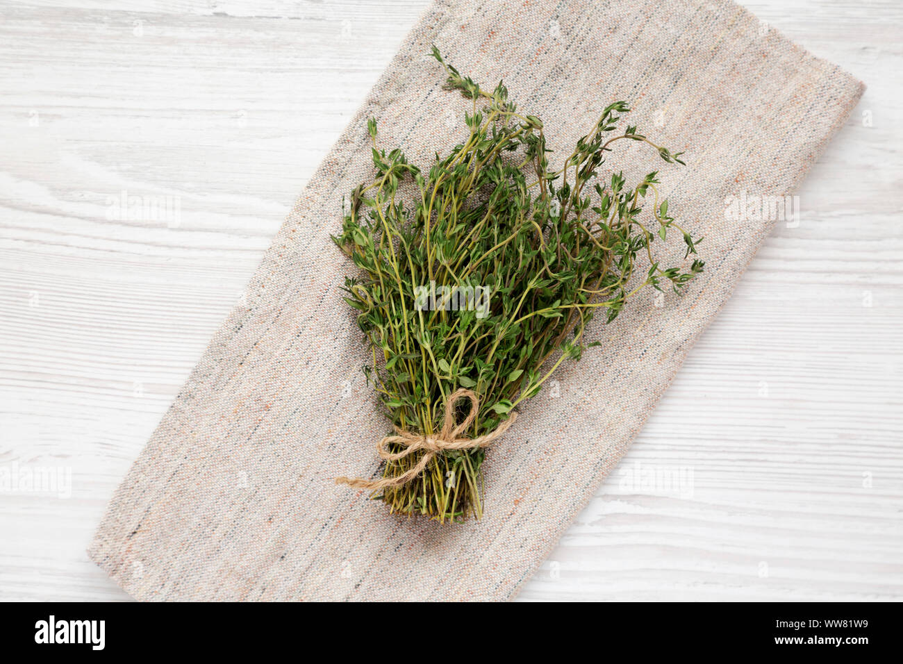Raw organic fresh thyme on cloth, overhead view. Flat lay, top view, from above. Close-up. Stock Photo
