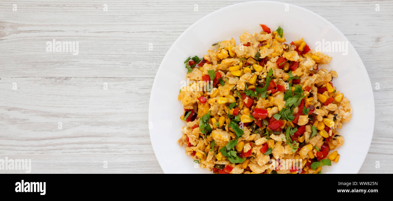 Homemade southwestern egg scramble on a white plate on a white wooden surface, overhead view. Flat lay, top view, from above. Copy space. Stock Photo