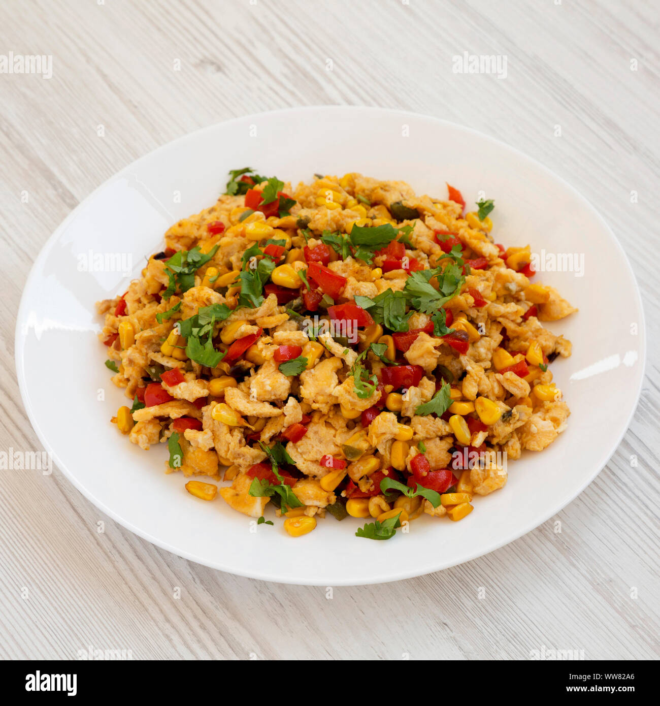 Homemade southwestern egg scramble on a white plate on a white wooden background, side view. Close-up. Stock Photo