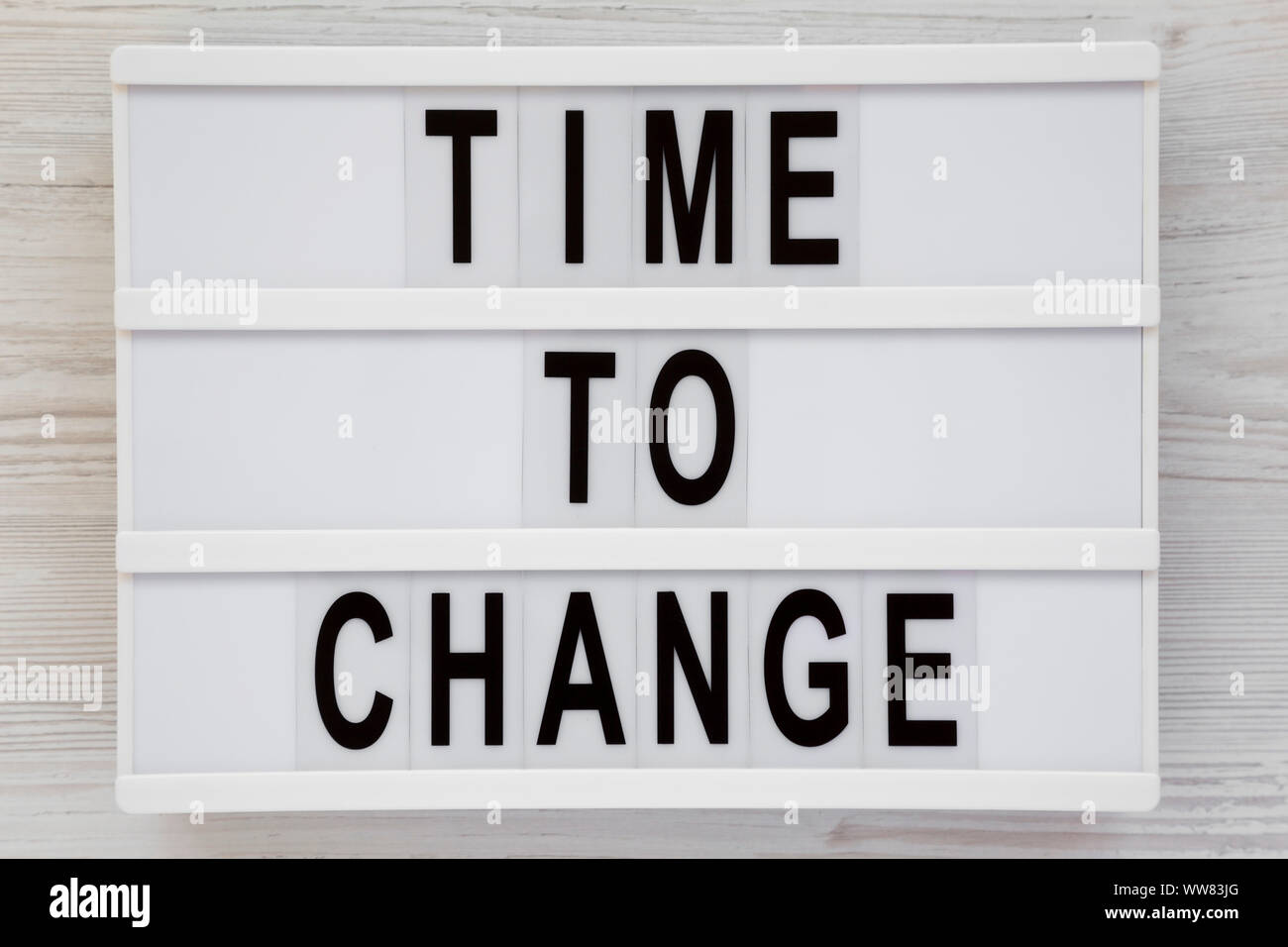 'Time to change' words on a lightbox over white wooden background, top view. Overhead, from above. Flat lay. Stock Photo