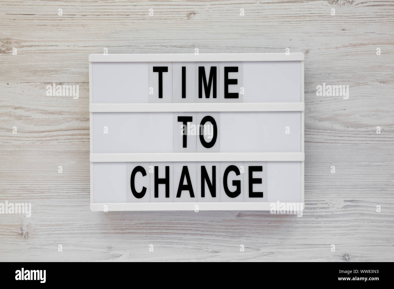 'Time to change' words on a modern board over white wooden surface, top view. Overhead, from above. Flat lay. Stock Photo