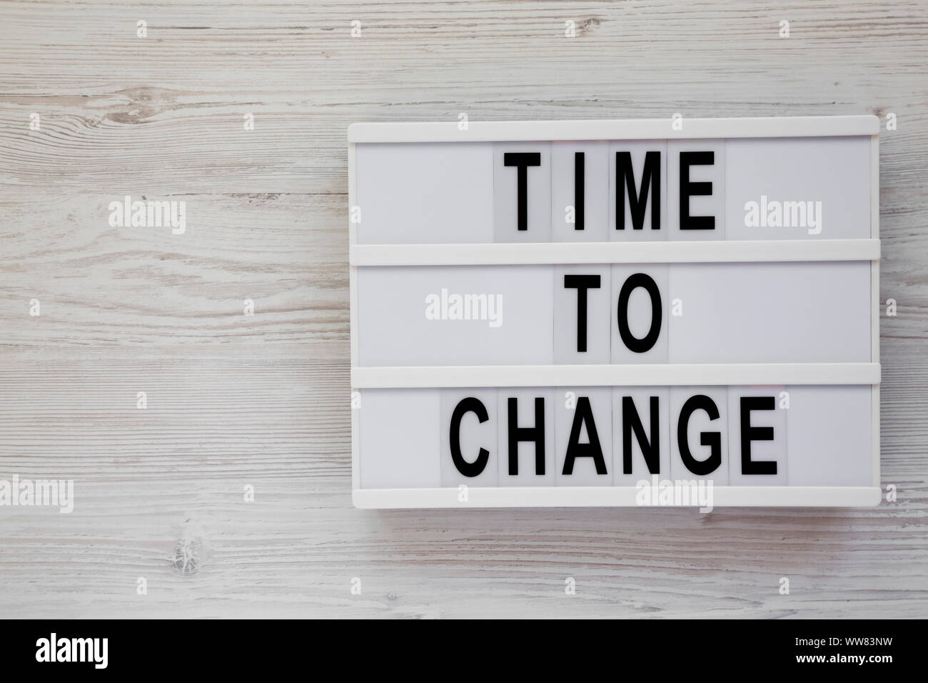 'Time to change' words on a modern board over white wooden background, top view. Overhead, from above. Flat lay. Copy space. Stock Photo