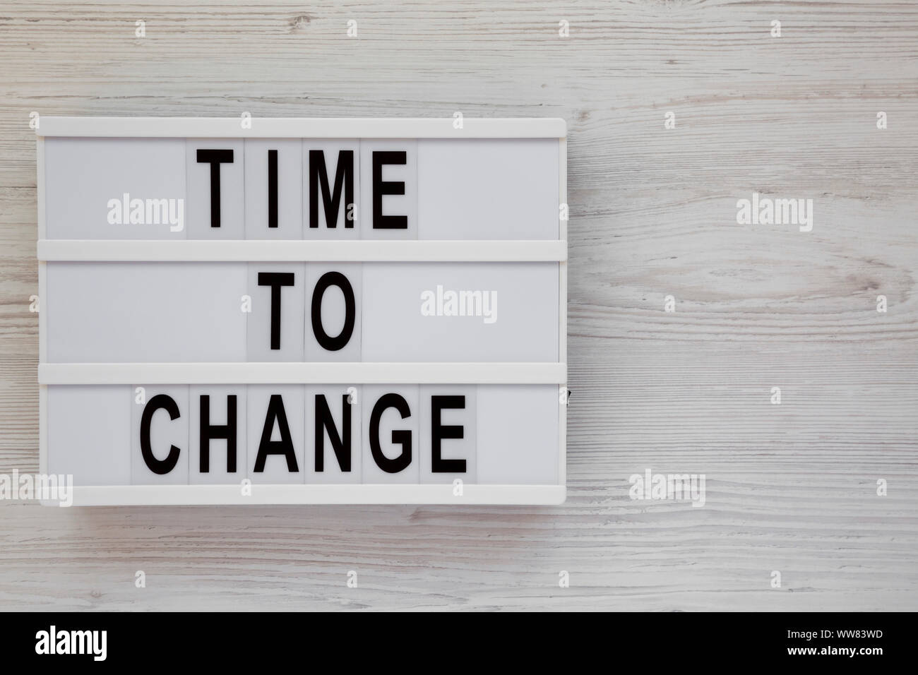 'Time to change' words on a modern board over white wooden surface, top view. Overhead, from above. Flat lay. Space for text. Stock Photo