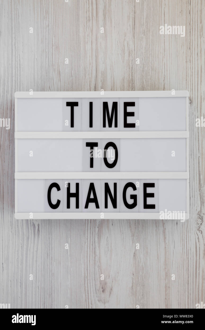 'Time to change' words on a lightbox over white wooden background, top view. Overhead, from above. Flat lay. Close-up. Stock Photo