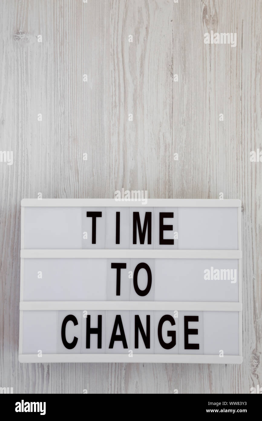 'Time to change' words on a modern board over white wooden surface, top view. Overhead, from above. Flat lay. Copy space. Stock Photo