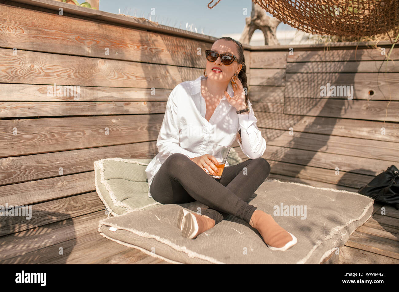 Young woman sitting on pillows at the dachgarten in Munich Stock Photo