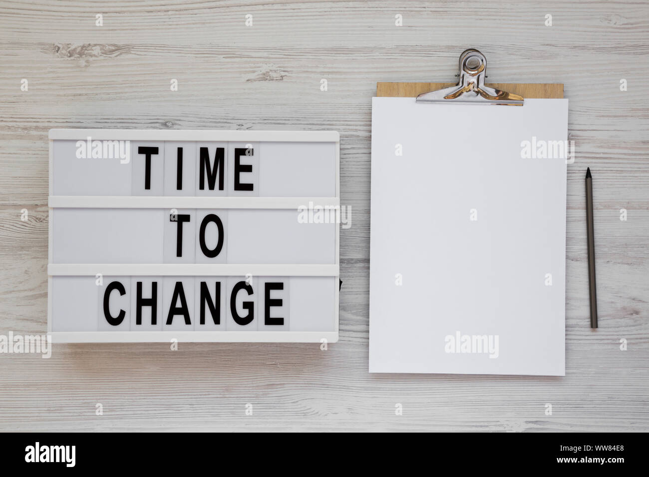 'Time to change' words on a modern board, clipboard with blank sheet of paper on a white wooden surface, top view. Overhead, from above. Flat lay. Cop Stock Photo