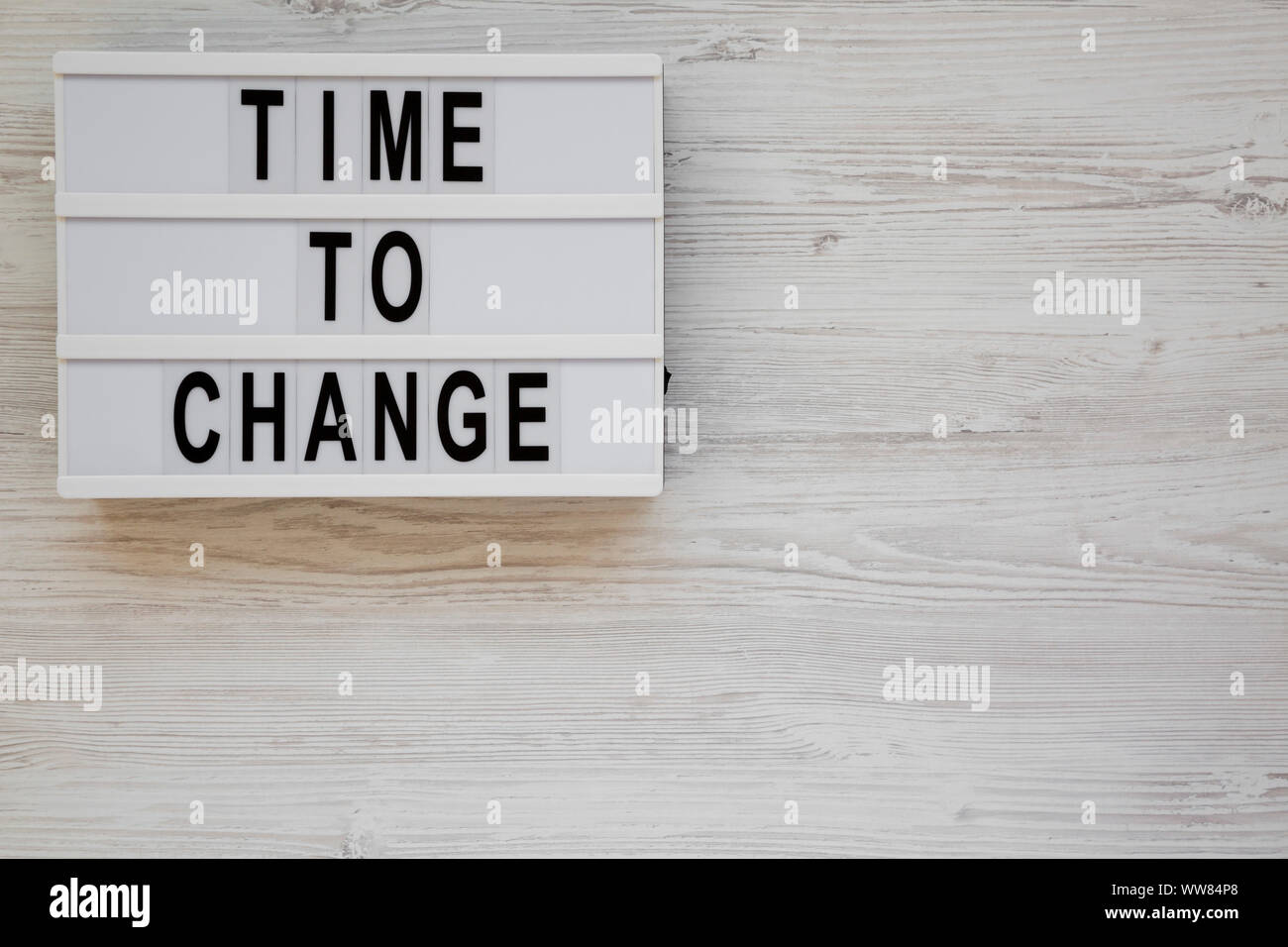 'Time to change' words on a lightbox on a white wooden background, top view. Overhead, from above. Flat lay. Copy space. Stock Photo