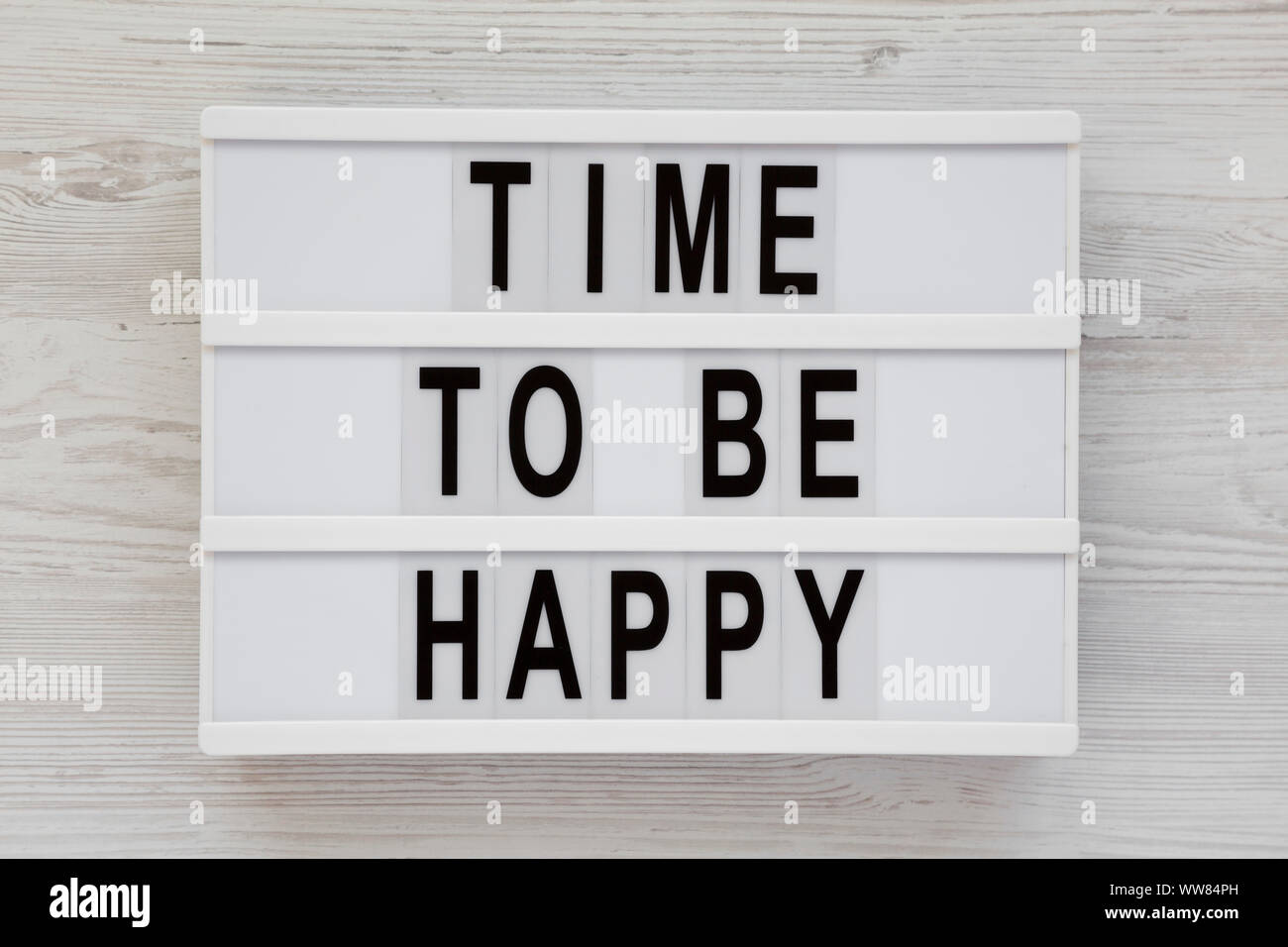 'Time to be happy' words on a modern board on a white wooden surface, top view. Overhead, from above. Flat lay. Close-up. Stock Photo