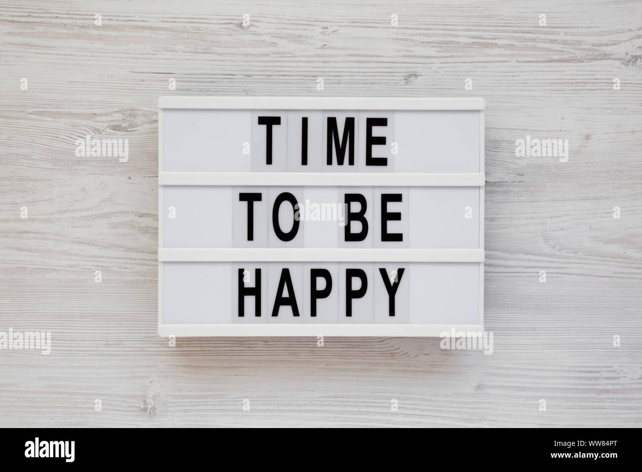 'Time to be happy' words on a modern board on a white wooden background, top view. Overhead, from above. Flat lay. Closeup. Stock Photo