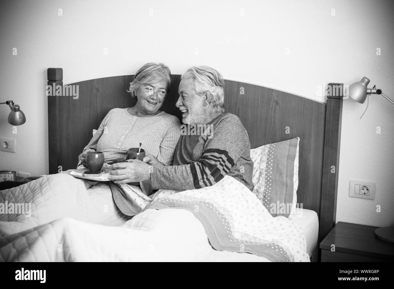 caucasian aged couple doing breakfast at home in the bed, nice natural scene at home for togetherness life concept, love and carefree people married, laughing together starting the day in the morning Stock Photo