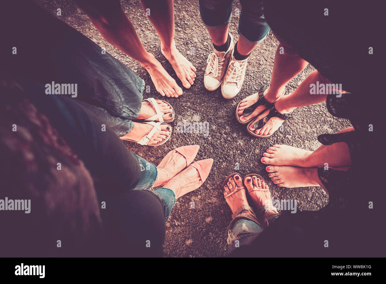 group of woman from high point of view with seven pair of feet with shoes and barefoot without. caucasian ladies in summer time. vintage colors and vignetting and shadow Stock Photo