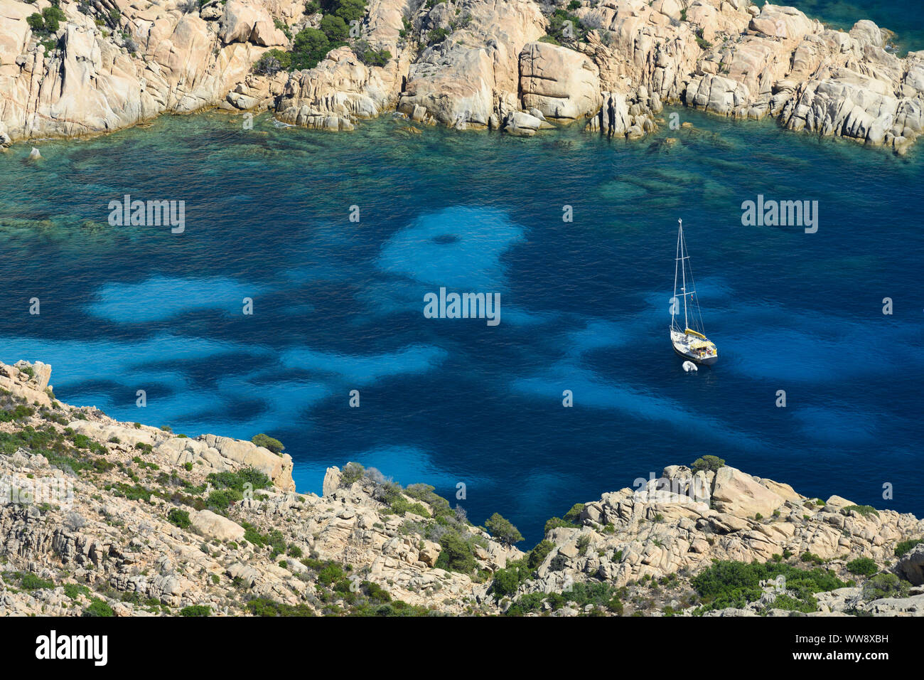 View from above, stunning aerial view of a sailboat floating on a turquoise clear water. Cala Coticcio (also known as Tahiti), Sardinia, Italy. Stock Photo