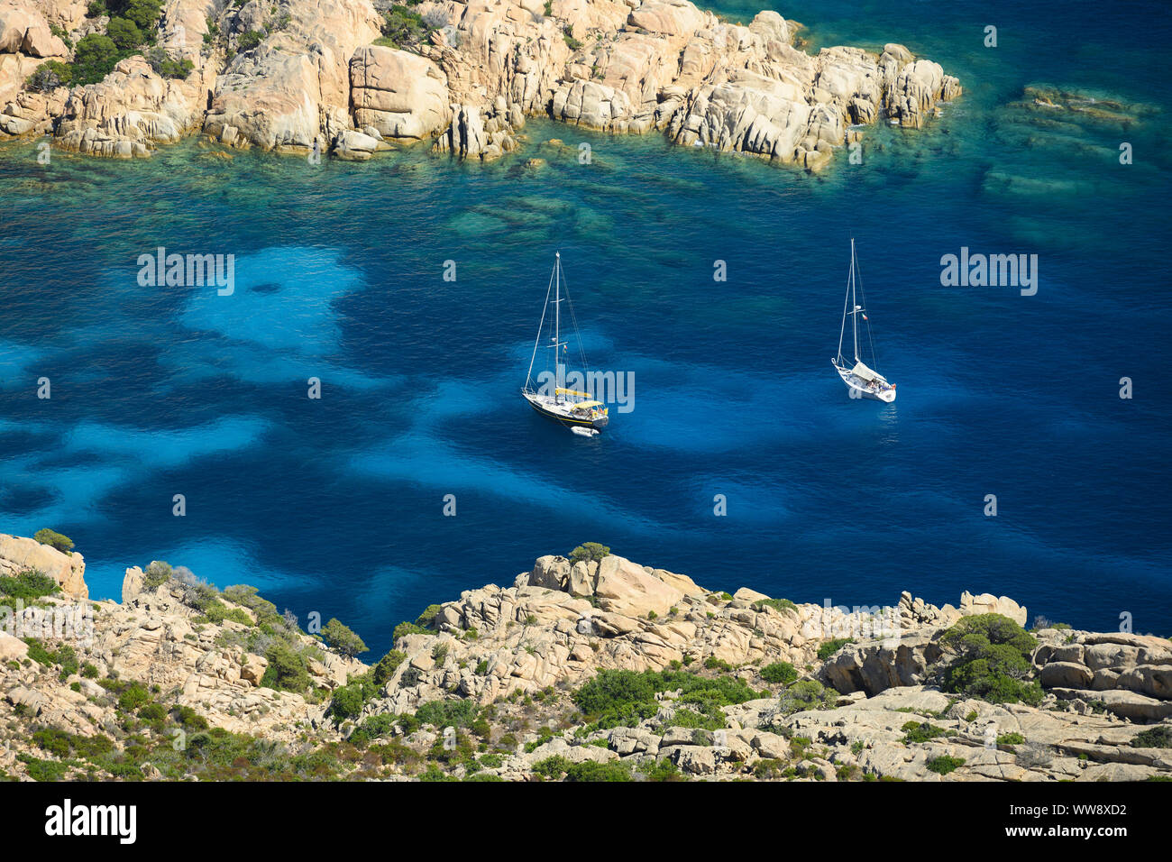 View from above, stunning aerial view of two sailboats floating on a turquoise clear water. Cala Coticcio (also known as Tahiti), Sardinia, Italy. Stock Photo