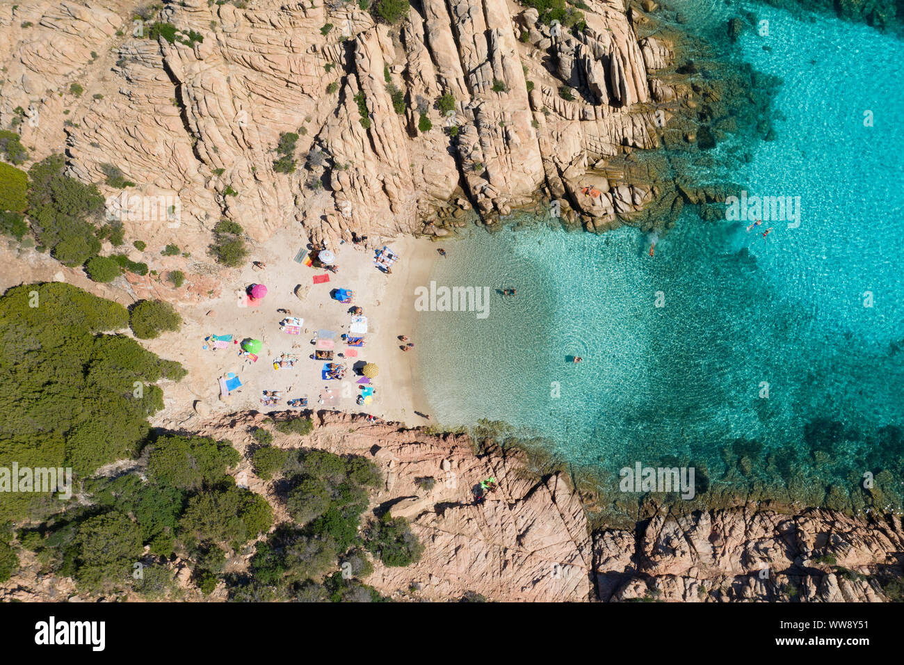 View from above, stunning aerial view of a small beach with beach umbrellas and people swimming in a turquoise clear water, Cala Coticcio, (Tahiti) Stock Photo