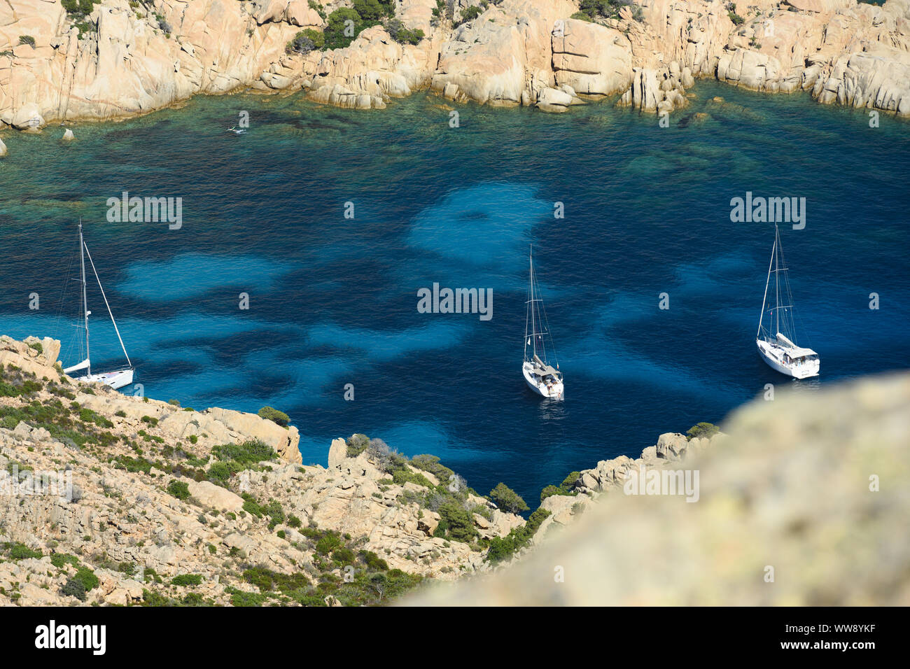 (Selective focus) View from above, stunning aerial view of three sailboats floating on a turquoise clear water. Cala Coticcio (also known as Tahiti). Stock Photo