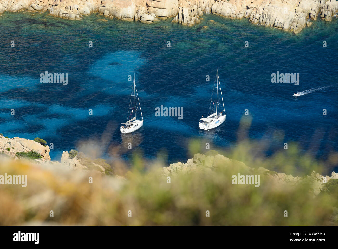 (Selective focus) View from above, stunning aerial view of two sailboats floating on a turquoise clear water. Cala Coticcio (also known as Tahiti). Stock Photo