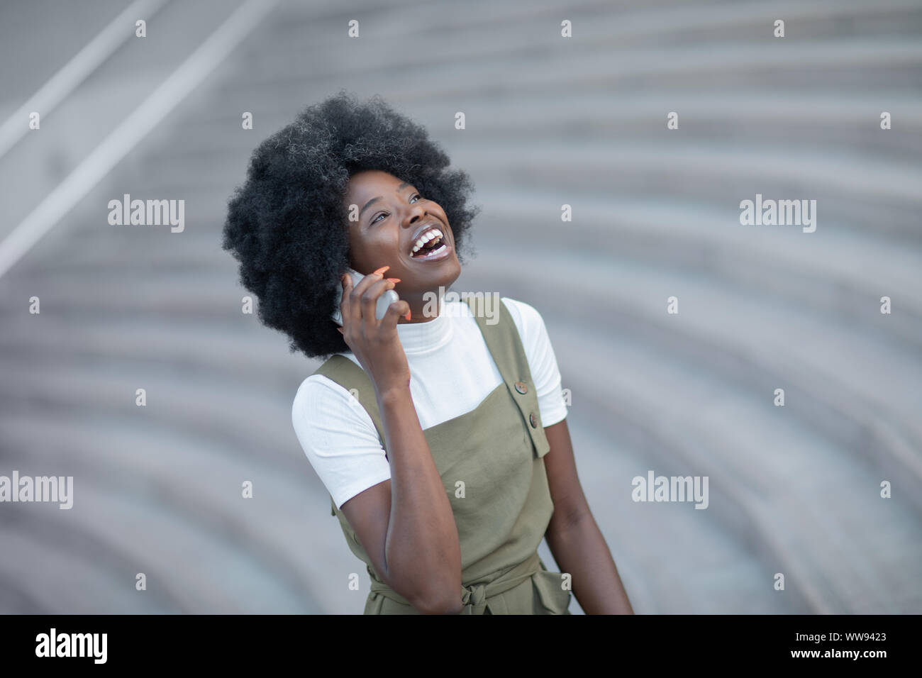 Happy young black woman calling by mobile phone outdoors in the city Stock Photo