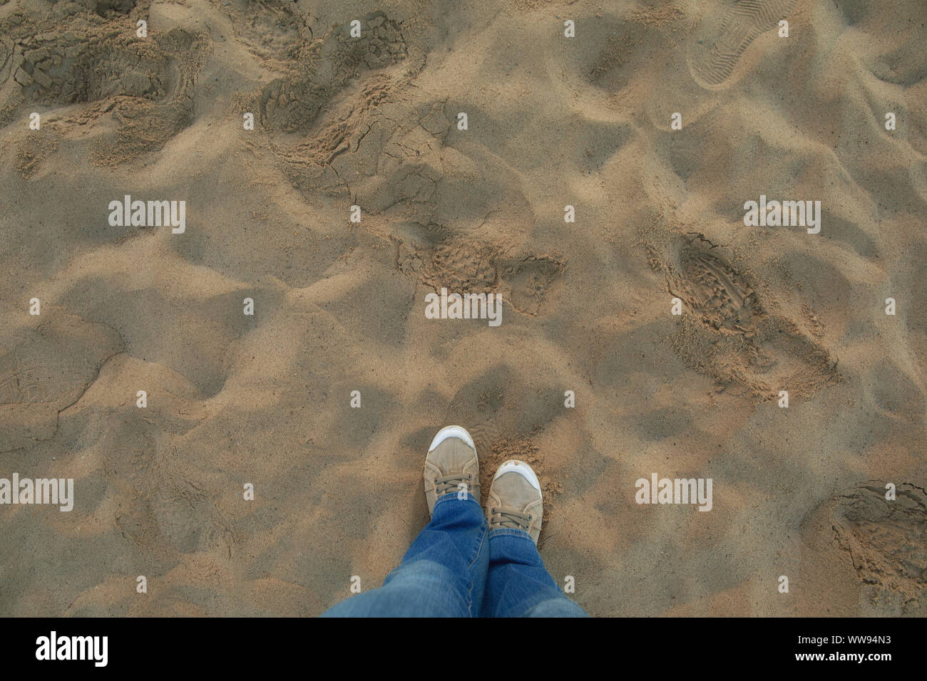A person in jeans and sneakers stands on sunny sandy beach. Personal perspective used. Stock Photo