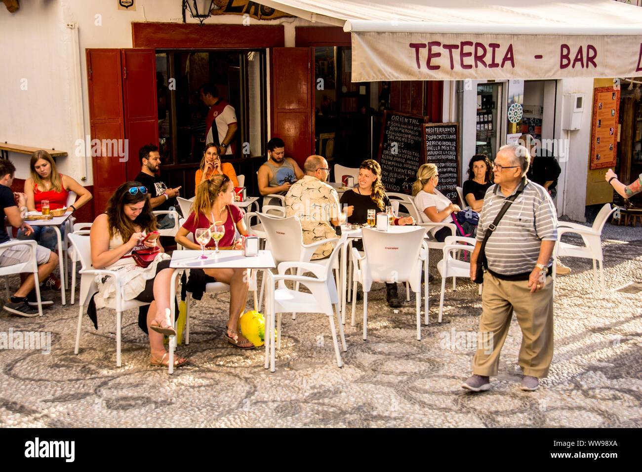 People eating at the Teteria Bar located in Granada, Spain. Stock Photo
