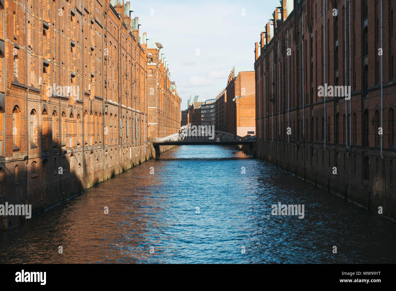 Looking down the canals with old warehouses on either side in the late afternoon in Hamburg, Germany Stock Photo