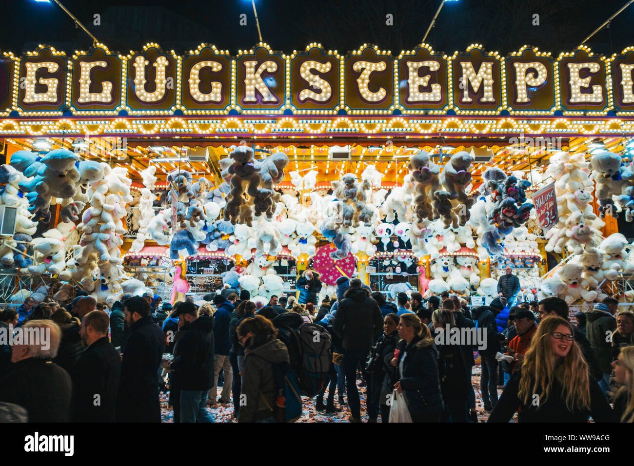 Dozens of stuffed toy animals hang above a raffle-like game while fair attendees walk past, one night at a fairground in Hamburg, Germany Stock Photo