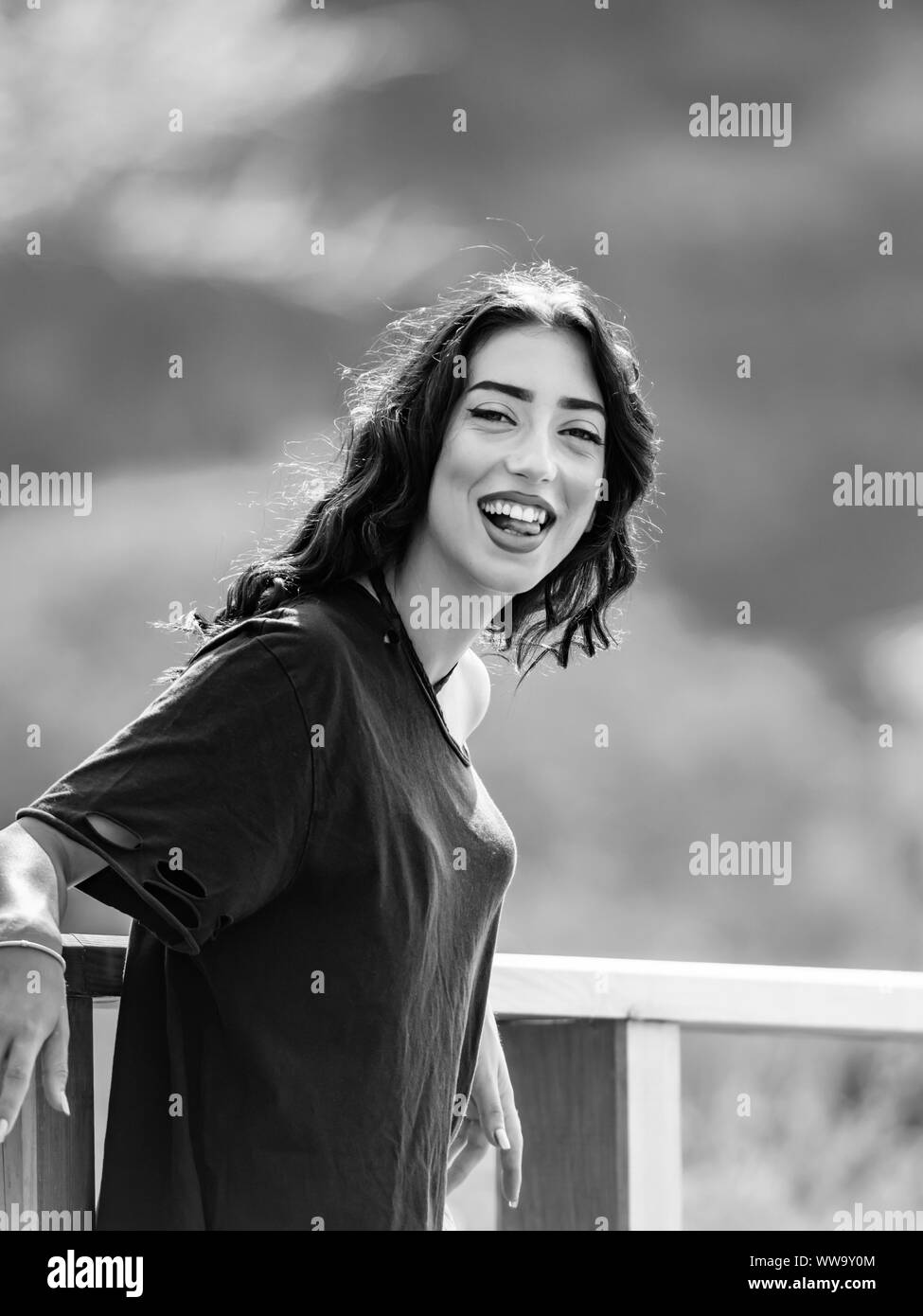 Teen girl is happy eyeshot eye eyes-contact looking at camera squinting squint B&W Black and White monochrome retro big smile Stock Photo