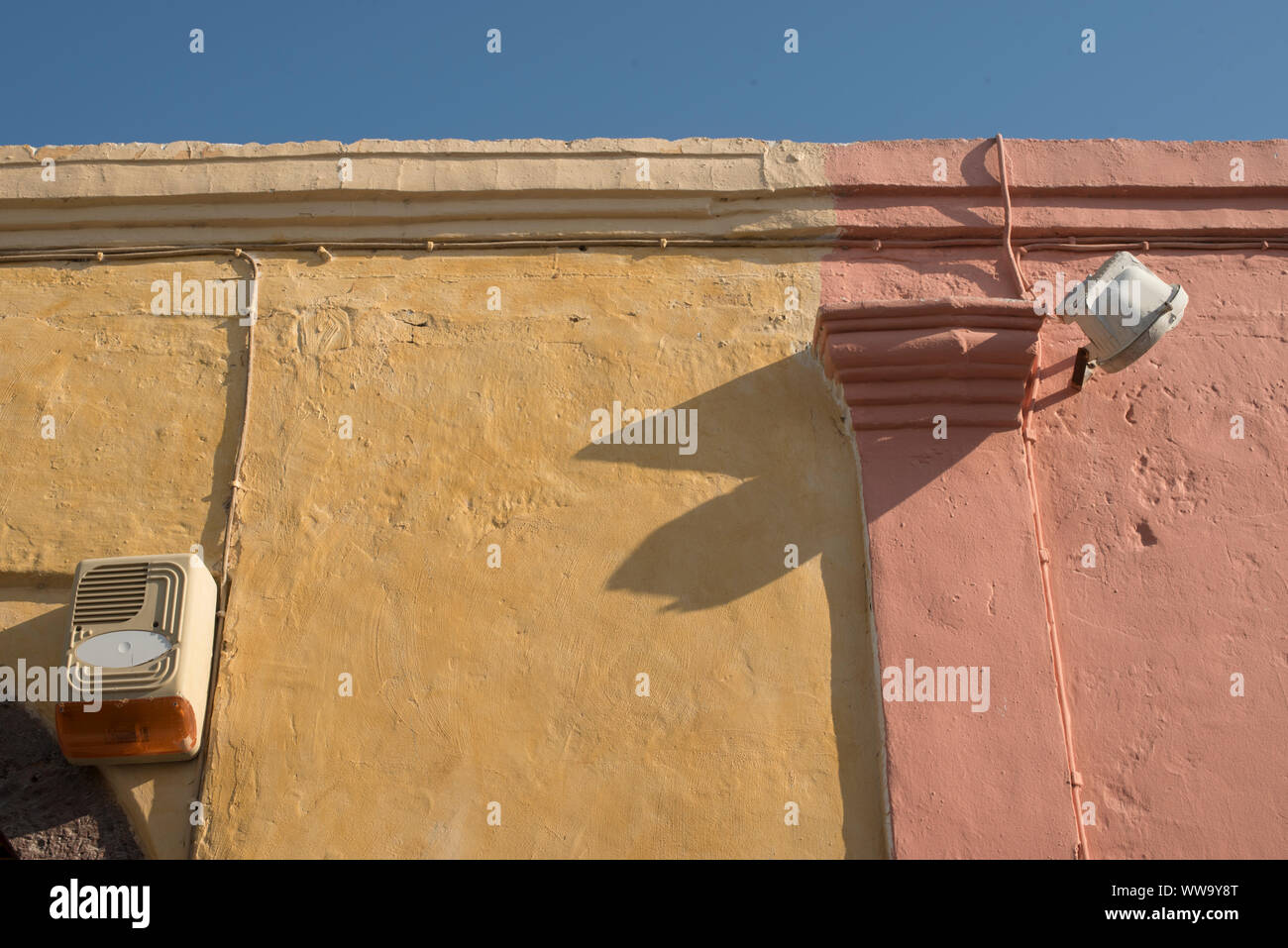 Santorini, Greece - June 24, 2018: Yellow and pink painted walls in the historic town of Oia, a popular tourist destination on the northern end of San Stock Photo