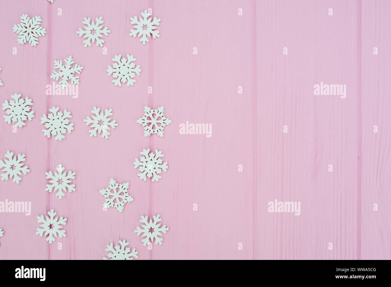 white christmas snowflakes decoration on pink wooden background with place for your text xmas wallpaper flat lay top view WWA5CG