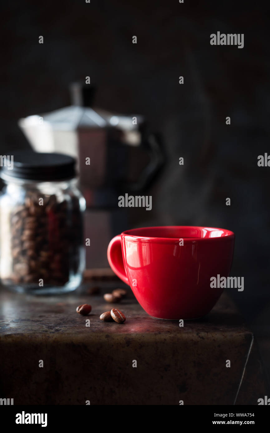 Red cup of coffee against dark background. Good morning concept Stock Photo