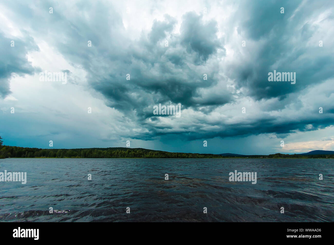 Dramatic sky over a lake close to Soderhamn and Hudiksvall in Sweden. Dark blue stormy clouds reflected in the dark water. Stock Photo