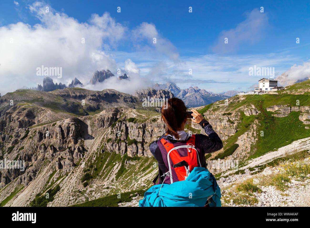 Girl photographing the Auronzo Refuge. Panoramic view of Cadini di Misurina and Auronzo refuge. Veneto Sesto Dolomites Italy Europe. Auronzo alpine hu Stock Photo