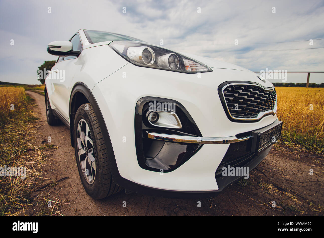 Ufa, Russia, 1 July, 2019: car Kia Sportage 2.0 CRDI awd or 4x4, white color, parked on the road, next to a large rock, with a beautiful blue sky in t Stock Photo