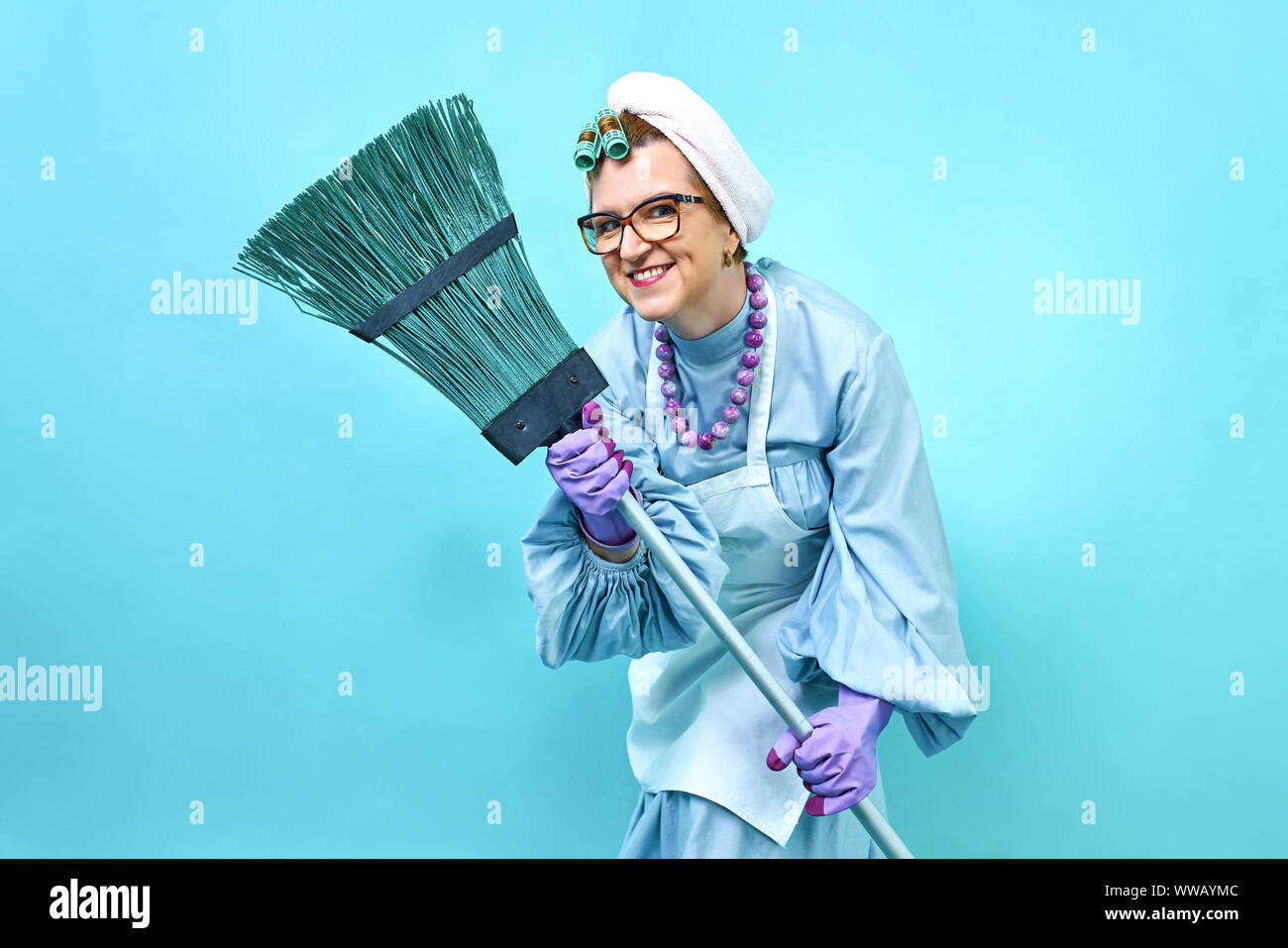 Cleaning Lady smile Fun. Elderly funny housewife fooling around with a broom. Full body isolated. Comical cleaning lady, old woman funky Stock Photo