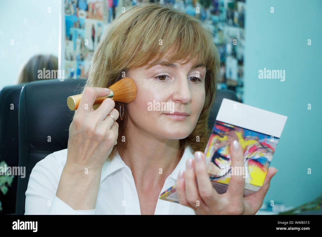 Close up of a mature blonde woman doing face makeup, selective focus Stock Photo