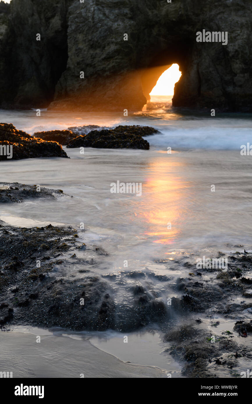 The sun sets through Harris Creek State Park sea arch just north of Brookings, Oregon, North America along the Pacific coast. Stock Photo