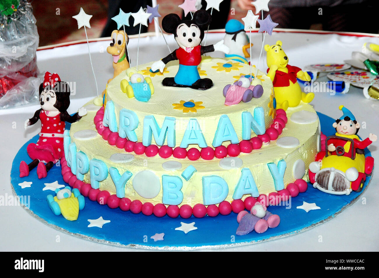 Colorful birthday cake decorated with little cartoon characters on the top. Stock Photo