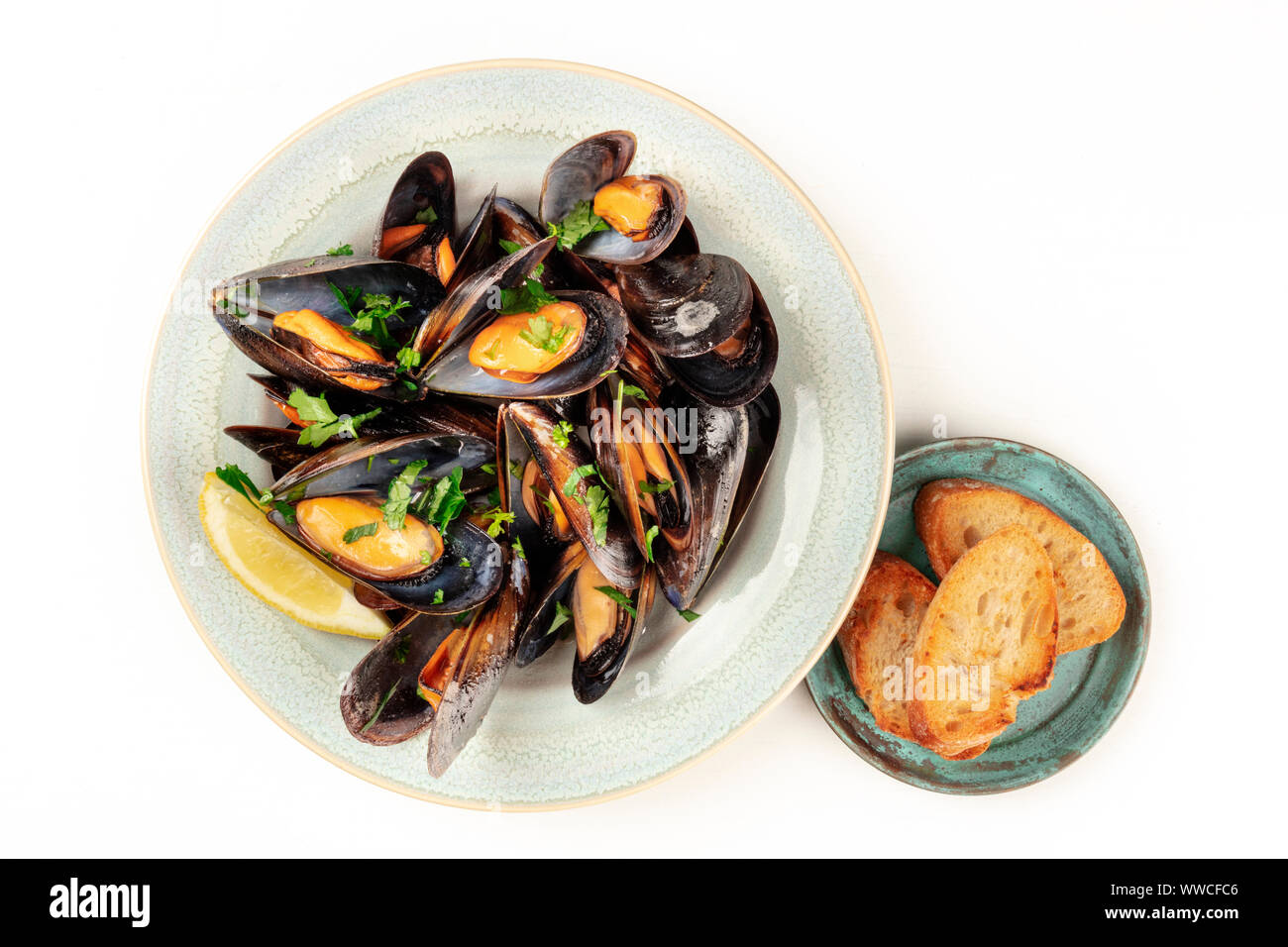Marinara mussels, shot from the top on a white background with toasted bread and copy space Stock Photo