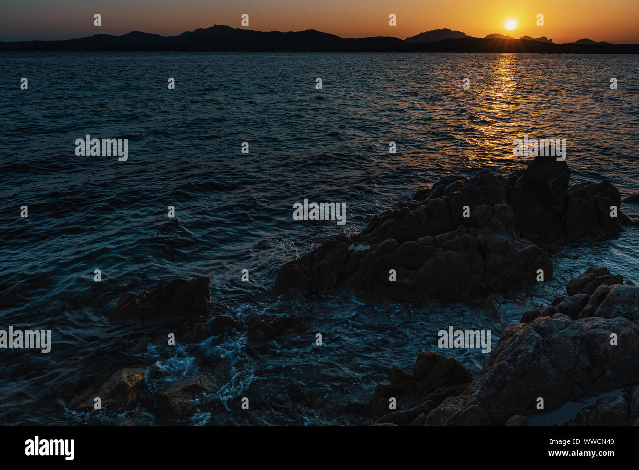 Beautiful mediterranean sunset with sunrays and rocks in the foreground Stock Photo