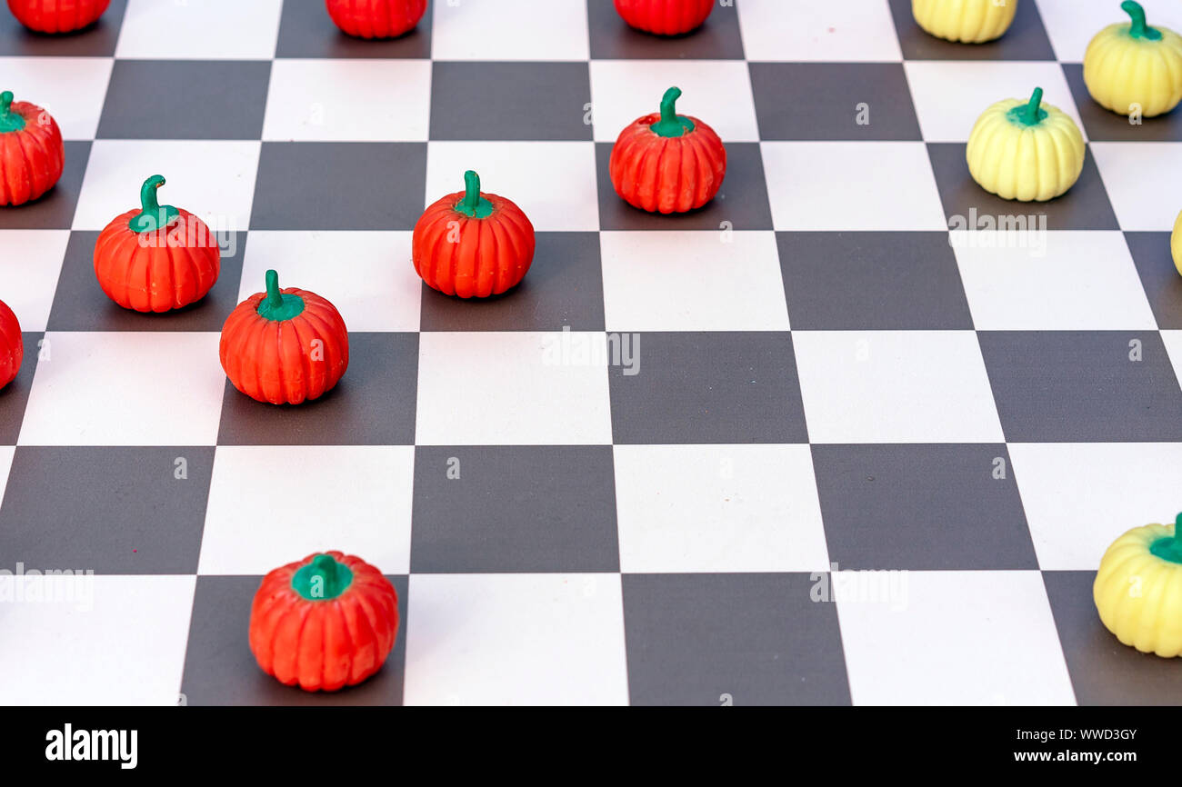 Game board with checkers in the form of orange and yellow pumpkins. Stock Photo