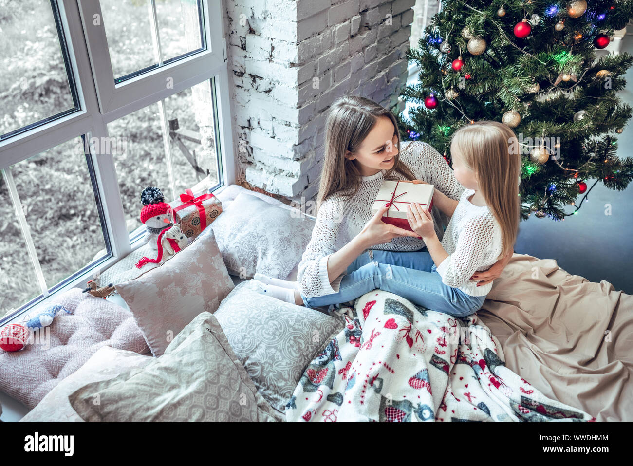 Girl Holding Gift Box Smiling And Sending Present To Mom Happy Child Girl Near A Christmas Tree With Christmas Present Bought From Shopping Sale Xma Stock Photo Alamy