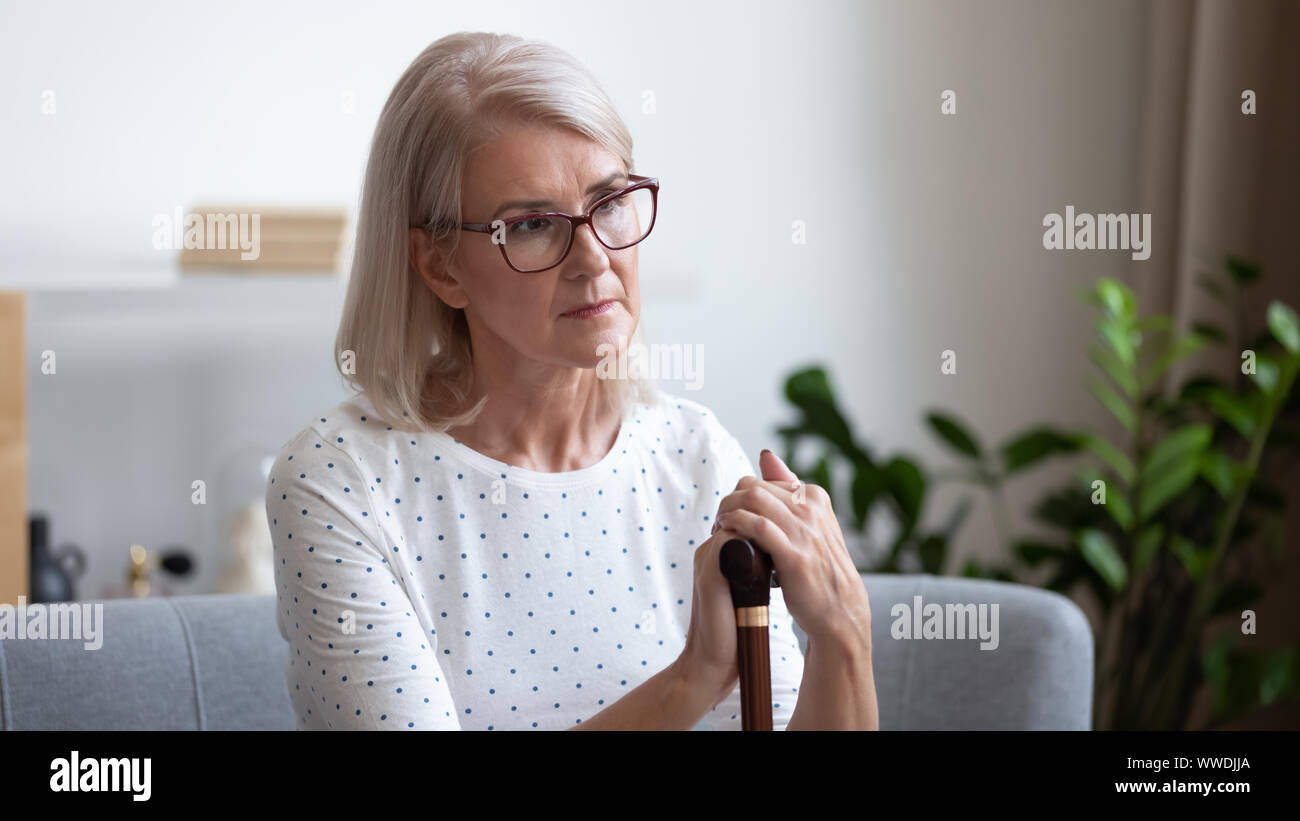 Upset mature woman holding wooden cane, thinking about future Stock Photo
