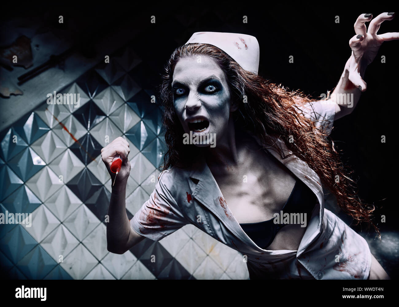 Horror shot: the terrible evil crazy nurse (doctor) attacking by bloody syringe. Zombie woman (living dead). Monster from nightmare Stock Photo