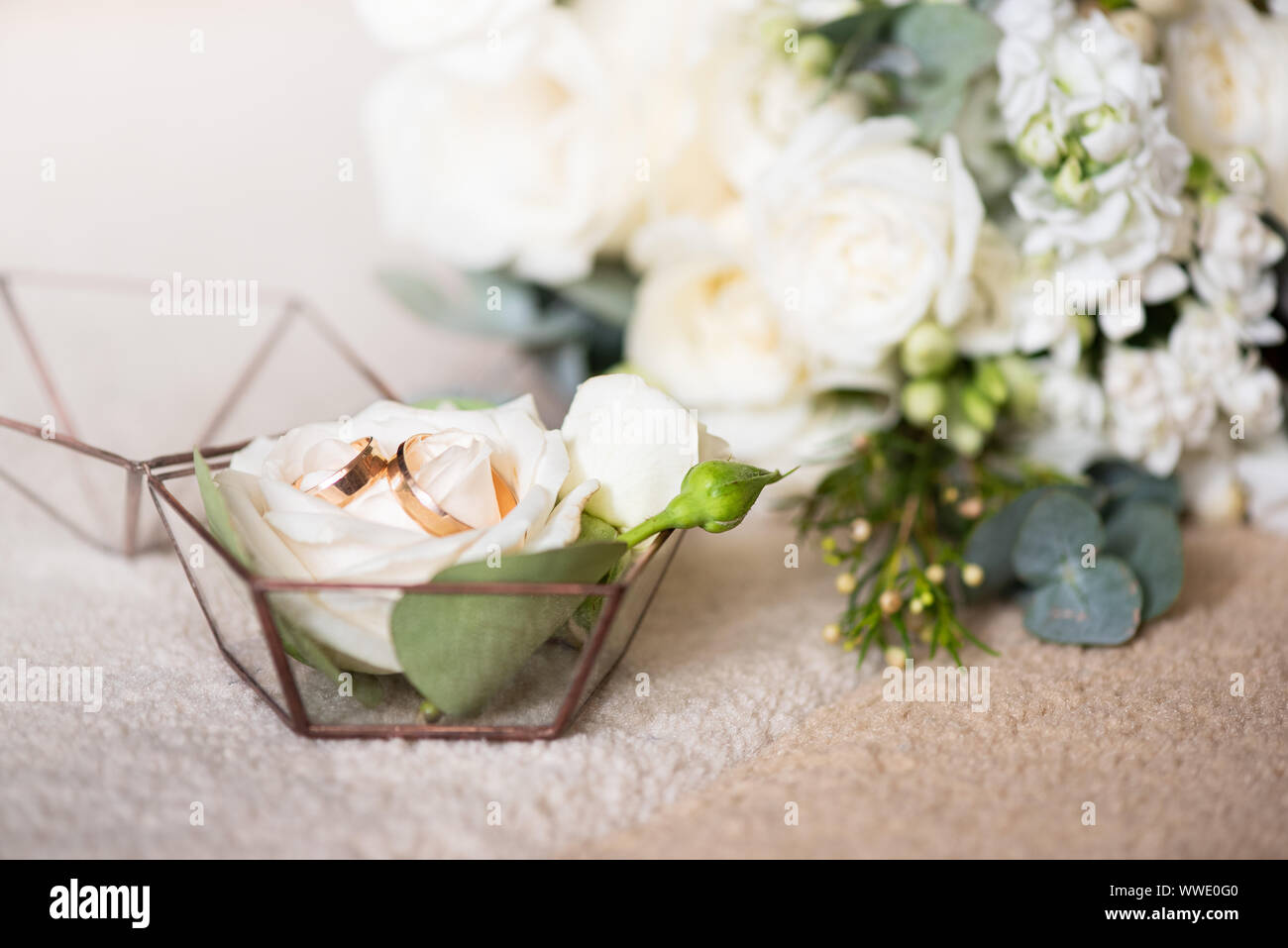 Two wedding rings in beautiful box and bouquet of flowers. Themes of engagement, declaration of love, wedding day, florist services. Stock Photo