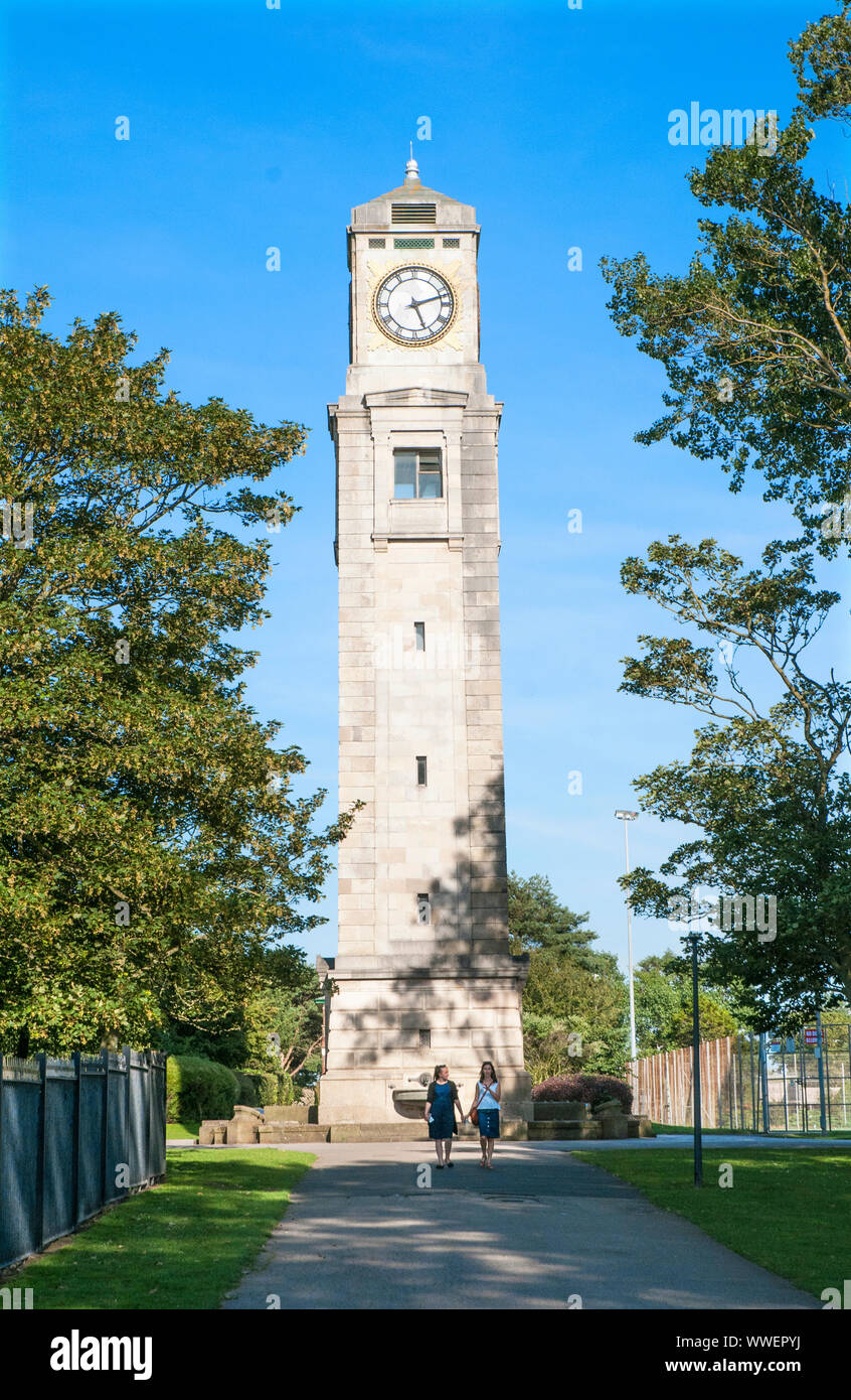 Two ladies walking in front of the Cocker Clock Tower on a sunny day in Stanley Park Blackpool Lancashire England UK. Stock Photo