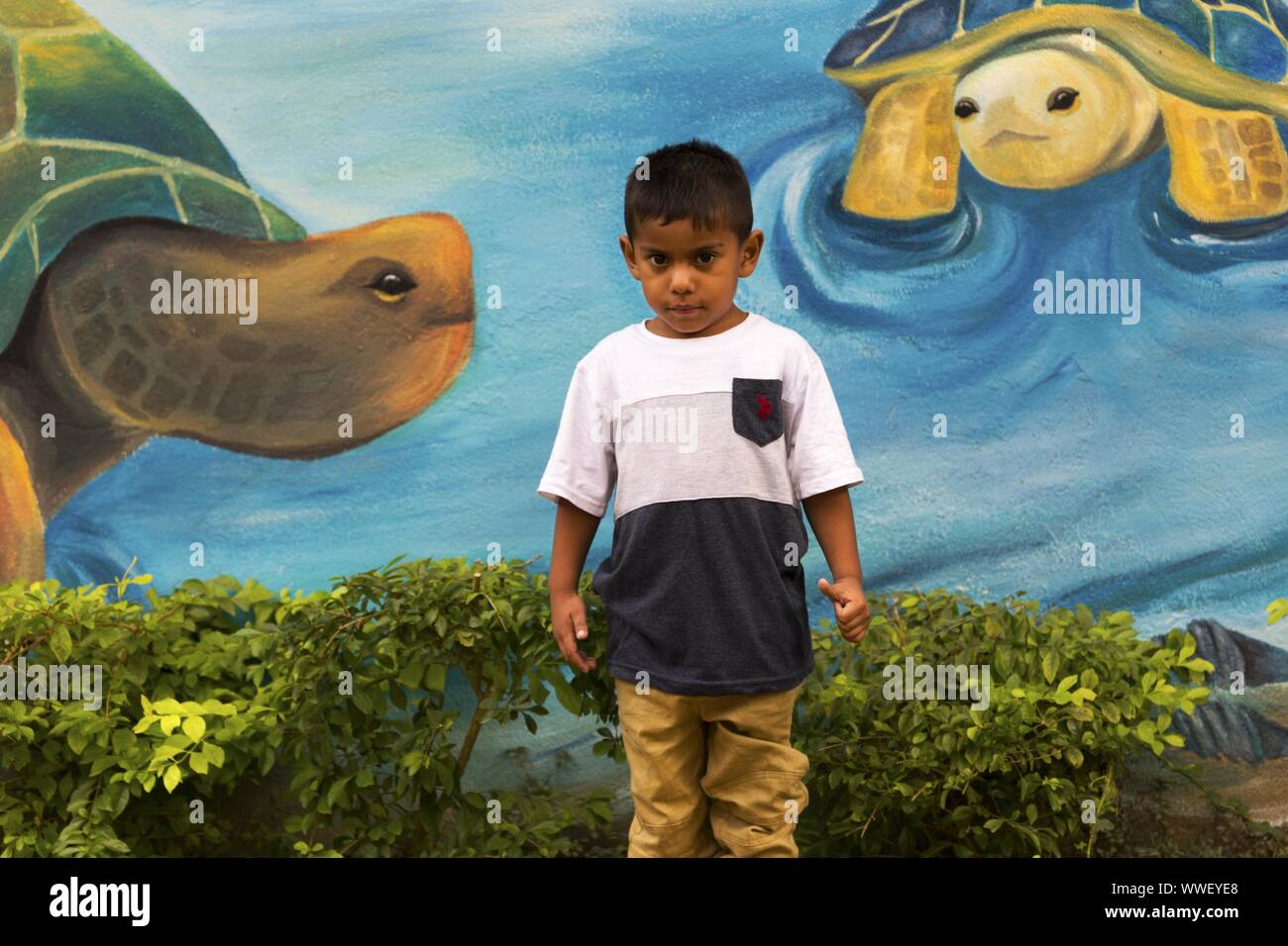 Young Male Child standing against the blue wall painted with Turtle Images in Rio Dulce Village, Guatemala Stock Photo