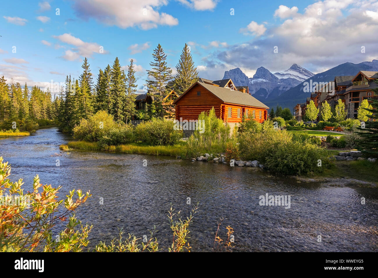 Spring Creek Alpine Village Landscape and Autumn Colors with Distant Three Sisters Mountain in Town of Canmore, Alberta Foothills of Canadian Rockies Stock Photo