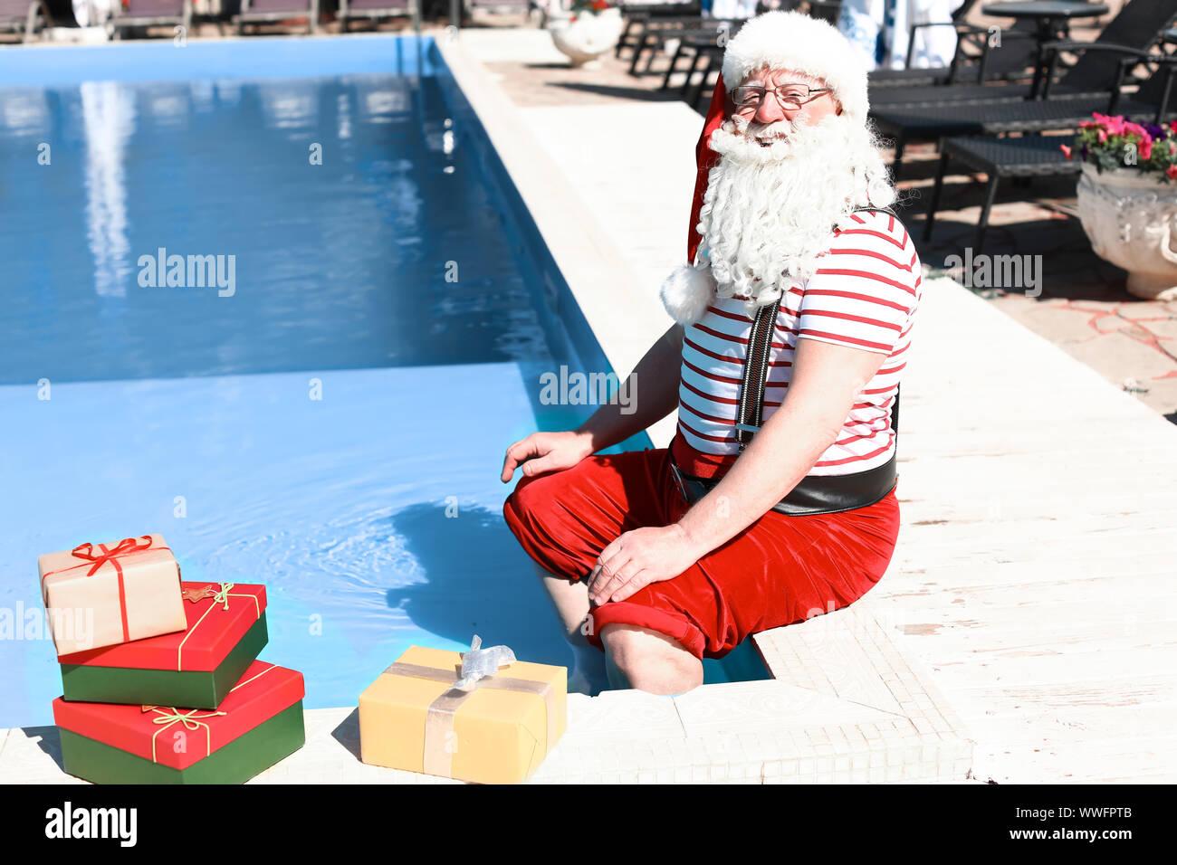 Santa Claus with gifts near swimming pool at resort Stock ...